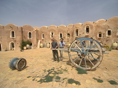 We are completely dwarfed by the massive wagon wheels; Ksar Ouled Dabbab