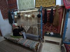 A lady hard at work on a carpet; Maison du Gouverneur