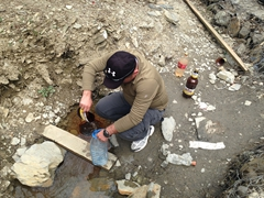 Khvicha getting naturally carbonated spring water in Svaneti