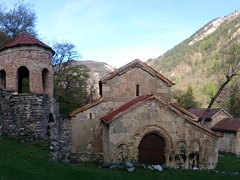 A monastery complex in the middle of the woods; mountains above Ertatsminda