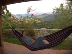 Becky relaxes in a hammock with a pleasent breeze and amazing views at Hosteria Izhcayluma; Vilcabamba
