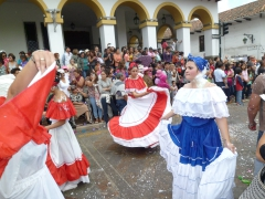 Dancers in traditional dresses flawlessly show off their dancing skills admidst all the foam spraying from celebrating spectators at the Carneval Parade; Cuenca