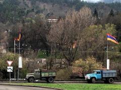 Armenian flags above old trucks in Dilijan